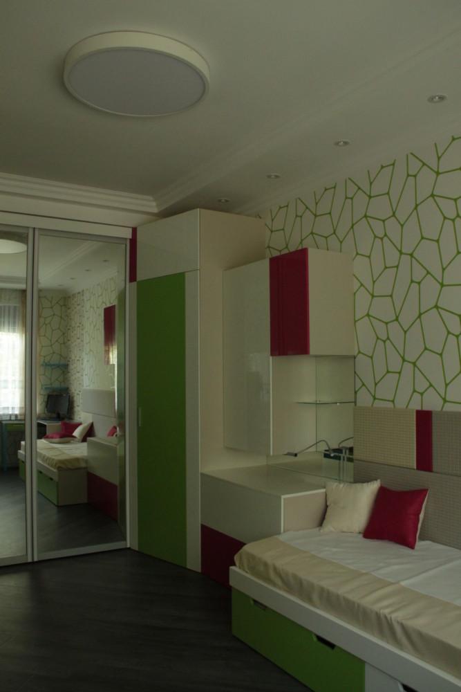 Гардеробный шкаф переходит на соседнюю стену в туалетный столик - прикроватную тумбу с ночником и кровать,далее композиция продолжается двумя рабочими столами у окна и завершается стеллажом с тв панелью.