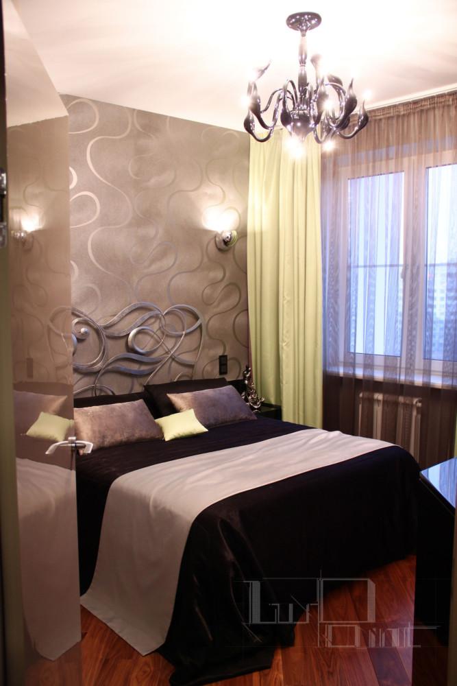 Хозяйская спальня. Итальянская кровать с витиеватым кованым изголовьем сочетается с аналогичным рисунком на обоях, удачно гармонирует с глянцевым покрытием люстры и черным бархатным покрывалом.