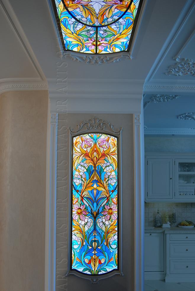 Витражи выполнены по мотивам замысловатых орнаментов Уильяма Морриса - пластичное переплетение растительных и цветочных образов.  Цветовая гамма выстроена на эффектном сочном сочетании желто-оранжевых оттенков и красочных синих тонов.