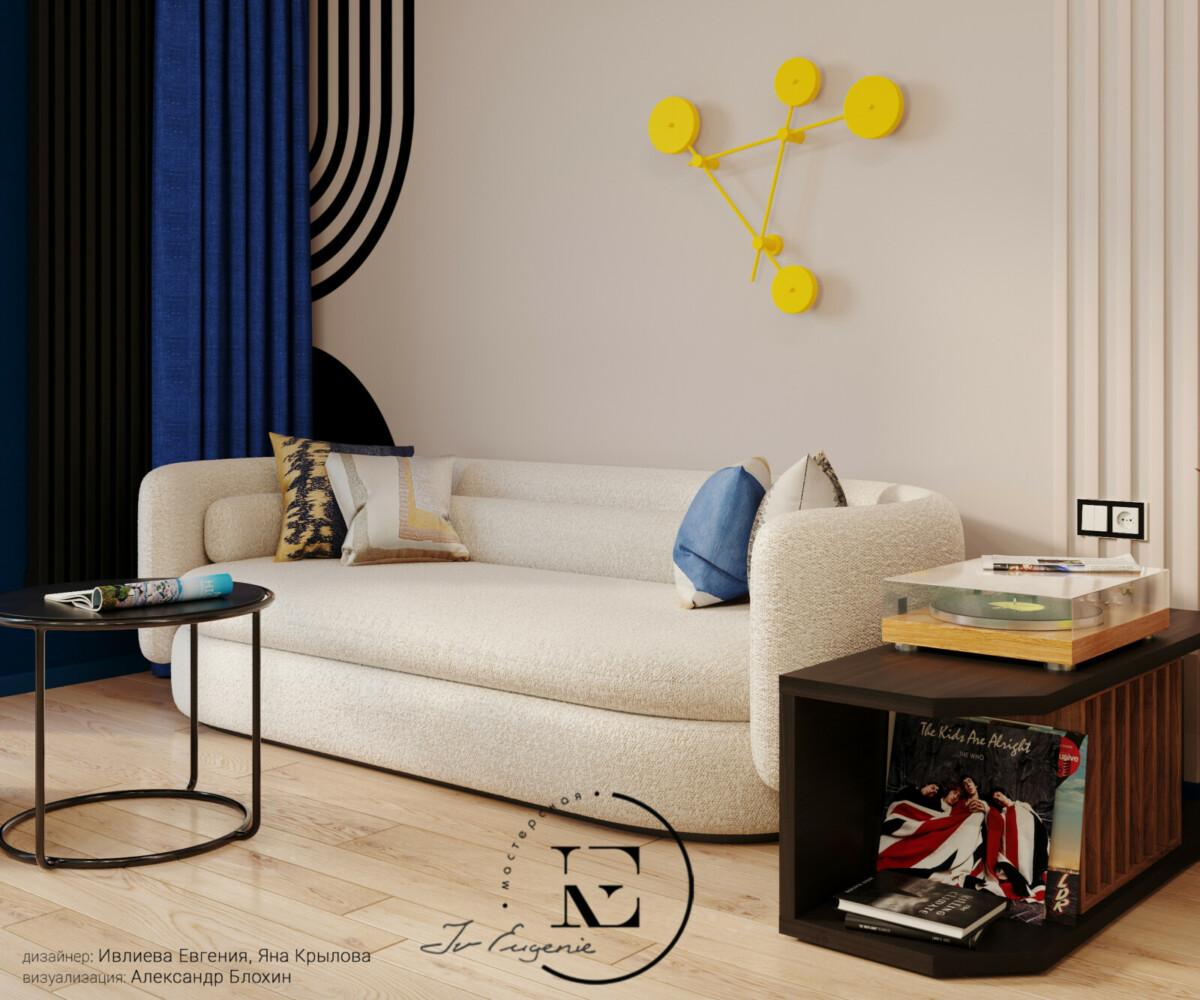 Зона отдыха в гостиной состоит из светлого дивана с яркими декоративными подушками и круглым журнальным столиком. Черная графика на стене хорошо сочетается с журнальным столиком и тумбой для хранения пластинок.