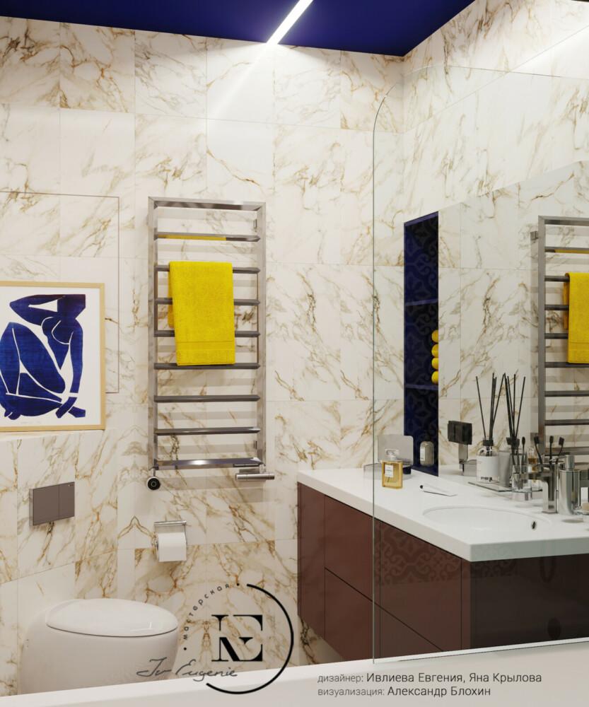 Мы видим  ванную комнату, выполненную в светлых тонах. Потолок, по замыслу дизайнера, выкрашен в ярко-синий цвет, в тон ему подобраны открытые полочки в угловой части помещения. Светлая плитка под мрамор хорошо сочетается с белой сантехникой. Пол из плитки с графичным рисунком и профильные светильники на потолке создают иллюзию движения.